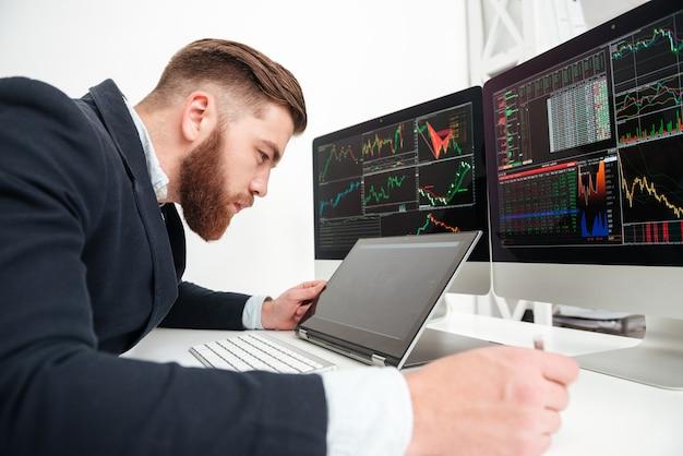 Geconcentreerde jonge zakenman die met computer op kantoor werkt