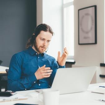 Geconcentreerde jongeman-operator in headset en vrijetijdskleding in gesprek met klant op laptop op kantoor