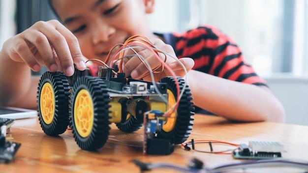 Geconcentreerde jongen die robot creëert bij laboratorium.