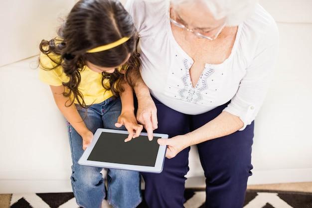 Geconcentreerde kleindochter die tablet met grootmoeder thuis gebruiken