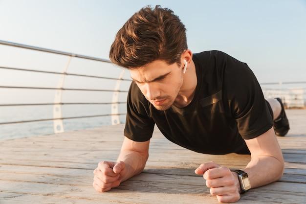 Geconcentreerde knappe jonge sportman die sportoefening beoefent