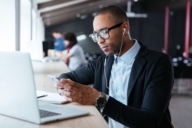 Geconcentreerde knappe jonge zakenman ontving tijdens het werkproces slecht nieuws op de smartphone