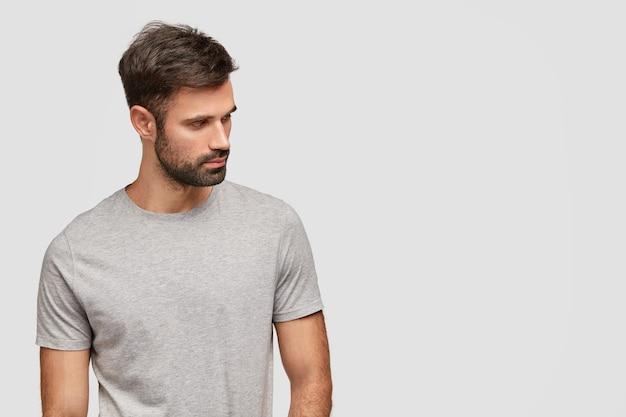 Geconcentreerde knappe ongeschoren jongeman foused opzij, heeft een gespierd lichaam, gekleed in een casual grijs t-shirt