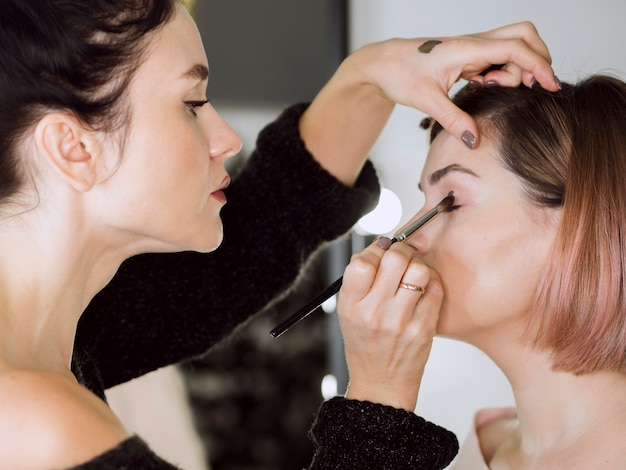Geconcentreerde kunstenaar die make-up doet