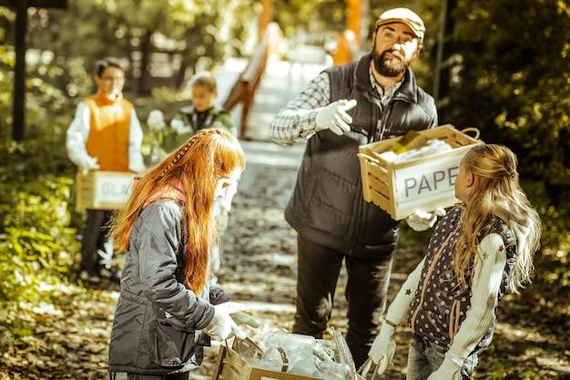 Geconcentreerde leraar orginazing het sorteren van afval in het bos op een goede dag