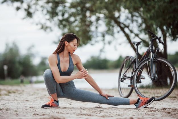 Geconcentreerde look. wielrenster met een goede lichaamsvorm die yoga-oefeningen doet en zich uitstrekt in de buurt van haar fiets op het strand overdag