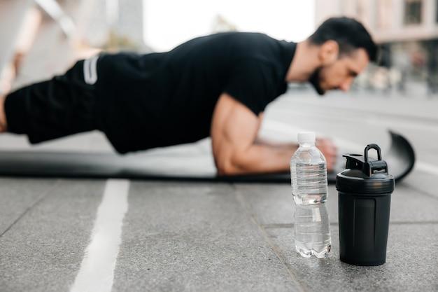 Geconcentreerde man die plankpositie doet tijdens het sporten op zwarte yogamat. waterflessen die dichtbij liggen. wazig man in zwarte sportkleding buitenshuis oefenen. ochtend opwarmen. zijaanzicht.