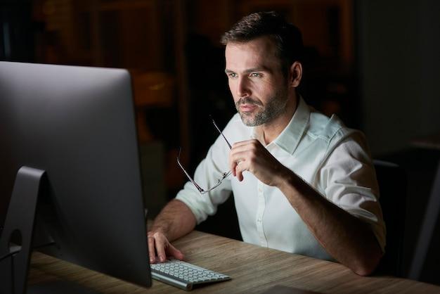 Geconcentreerde man die 's nachts computer gebruikt
