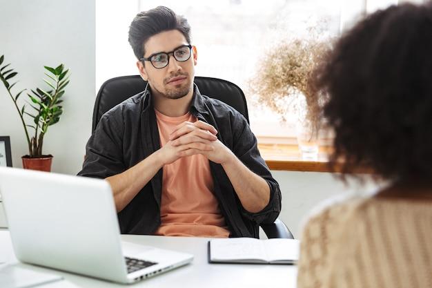 Geconcentreerde man in bril zittend op ontmoeting met zijn collega op kantoor