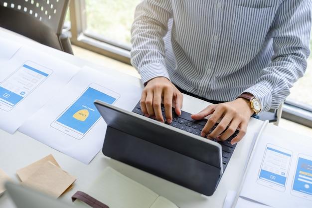 Geconcentreerde man in casual werken of typen op slimme toetsenbordtablet voor het ontwerpen, coderen, programmeren van mobiele applicatie.
