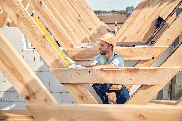 Geconcentreerde man met een helm die een waterpasinstrument vasthoudt aan een diagonale houten rail