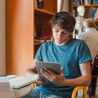 Geconcentreerde man met tablet in handen