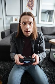 Geconcentreerde man om thuis te zitten spelen spelletjes