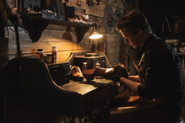 Geconcentreerde man schoenmaker op schoeisel workshop.