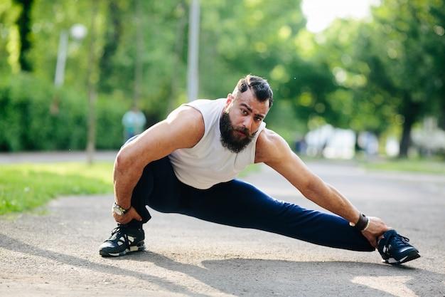 Geconcentreerde man strekt zijn linkerbeen