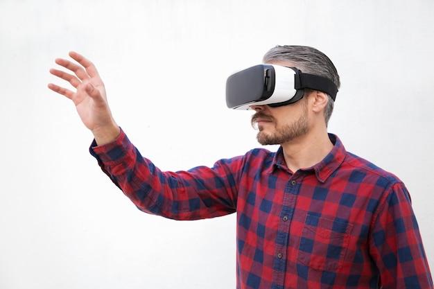 Geconcentreerde man van middelbare leeftijd in vr-headset aanraken van lucht