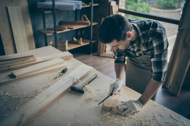 Geconcentreerde man verwerking houten hart met beitel polijsten in handschoenen werken met bouwgereedschap