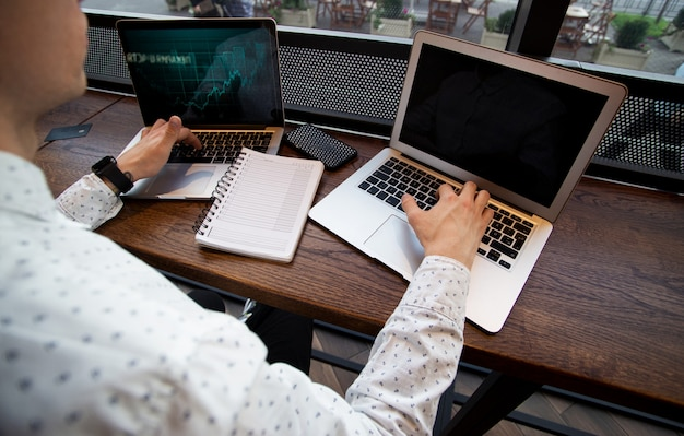 Geconcentreerde man werkt op zijn laptops