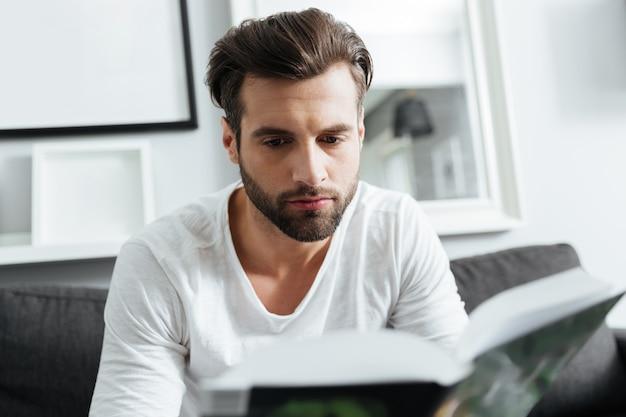 Geconcentreerde man zittend op de bank leesboek