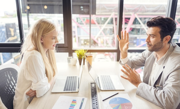 Geconcentreerde mannelijke en vrouwelijke werknemers zitten aan een bureau te onderhandelen met behulp van een laptop om ideeën te bespreken, diverse collega's praten brainstormen om samen te onderhandelen over een zakelijk project. samenwerkingsconcept:
