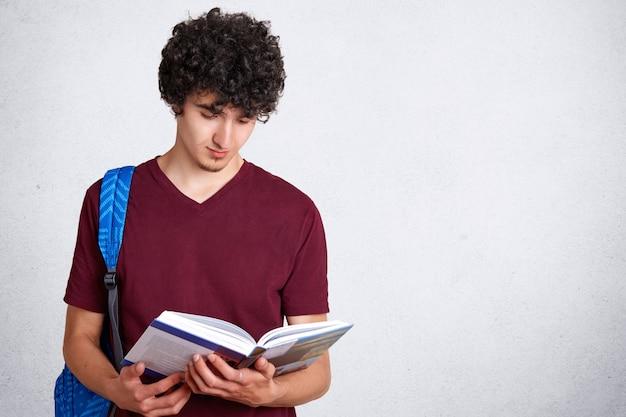 Geconcentreerde mannelijke hipster leest aandachtig wetenschappelijke literatuur, houdt boek, draagt rugzak