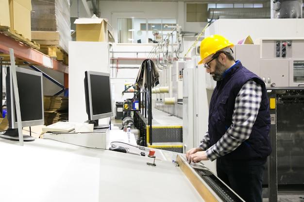 Geconcentreerde mannelijke ingenieur in glazen die machine in werking stellen