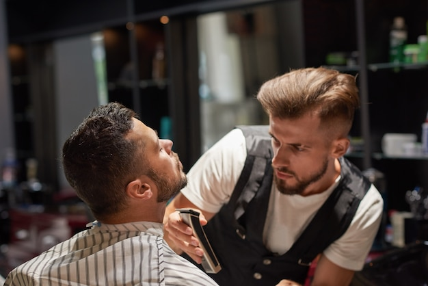 Geconcentreerde mannelijke kapper bedrijf trimmer in handen.