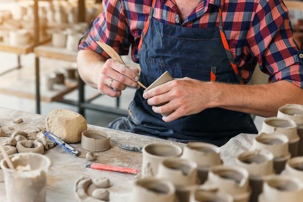 Geconcentreerde mannelijke pottenbakker die iets van klei maakt.