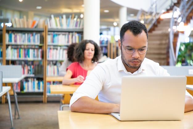 Geconcentreerde mannelijke volwassen student die aan computer in klaslokaal werkt