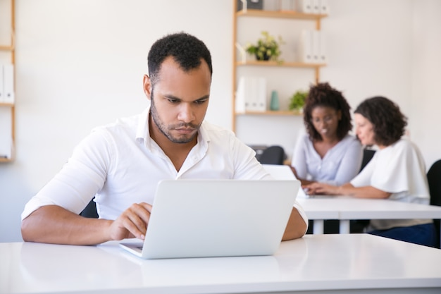 Geconcentreerde mannelijke werknemer die laptop in bureau met behulp van