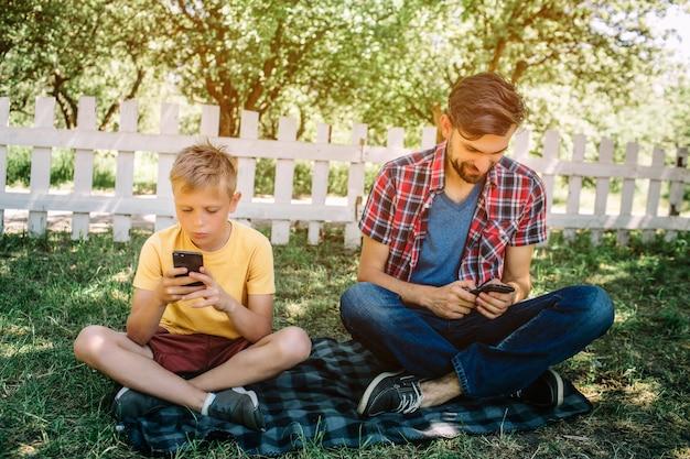 Geconcentreerde mannen zitten op de deken met gekruiste benen en kijken naar hun telefoons