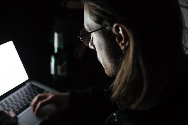 Geconcentreerde mens die laptop computer thuis binnen met behulp van