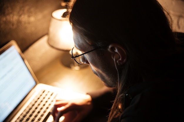 Geconcentreerde mens die laptop computer thuis met behulp van