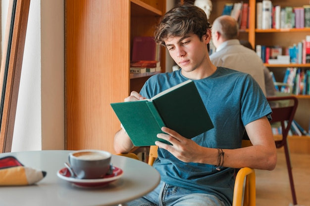 Geconcentreerde mens die lezingsboek geniet van