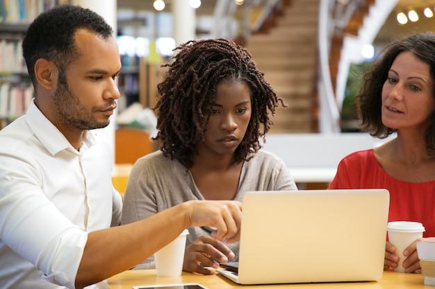 Geconcentreerde mensen die bij bibliotheek werken