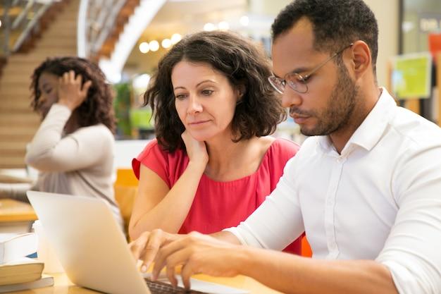 Geconcentreerde mensen die informatie lezen van laptop