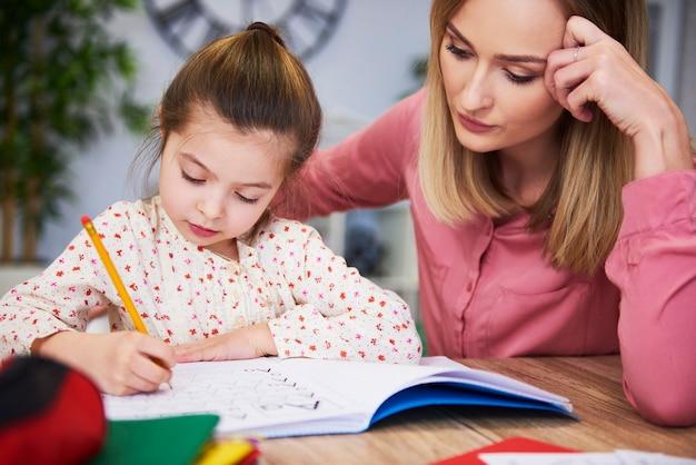 Geconcentreerde moeder die kind helpt met huiswerk