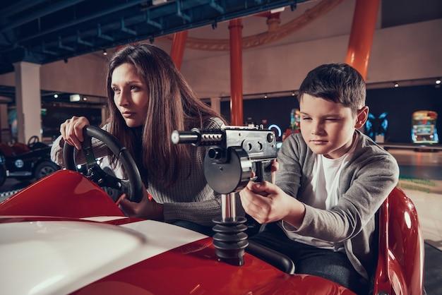 Geconcentreerde moeder en zoon rijden speelgoedauto in winkelcentrum