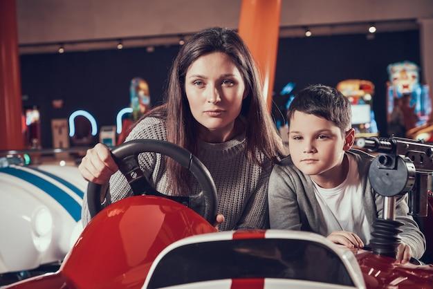 Geconcentreerde moeder en zoon speelgoedauto rijden.