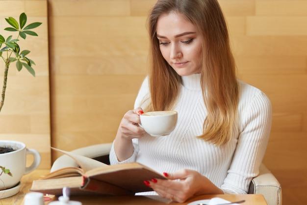 Geconcentreerde mooie jonge vrouw leest boek met kopje cappuccino, gericht op lezen, geniet van interessante spannende roman