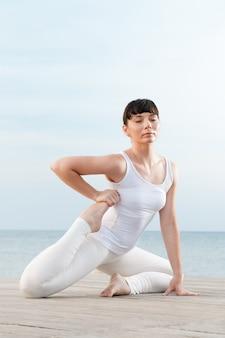 Geconcentreerde mooie vrouw doet yoga buiten op zee