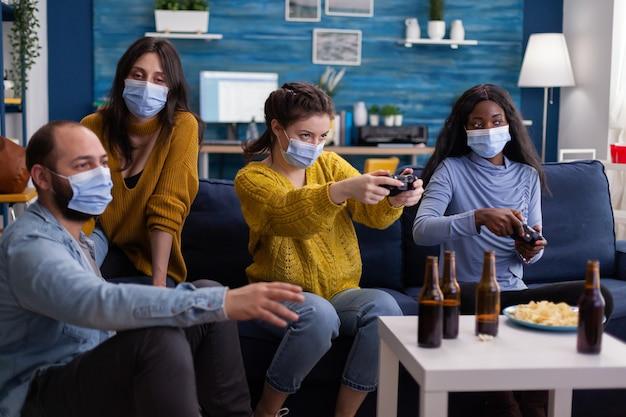 Geconcentreerde multi-etnische vrienden die proberen te winnen bij videogames tijdens sociale pandemie die gezichtsmasker dragen en afstand houden om corona niet te verspreiden zittend op de bank in de woonkamer.