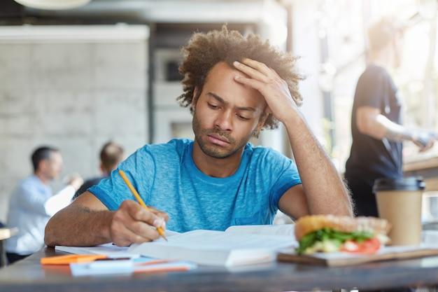 Geconcentreerde, nonchalant geklede, ongeschoren student met een donkere huid die studeert in een coffeeshop, opschrijft in een oefenboek, onderzoek doet of zich voorbereidt op een examen op de universiteit, serieus kijkt