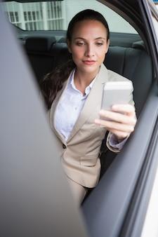 Geconcentreerde onderneemster die haar telefoon met behulp van