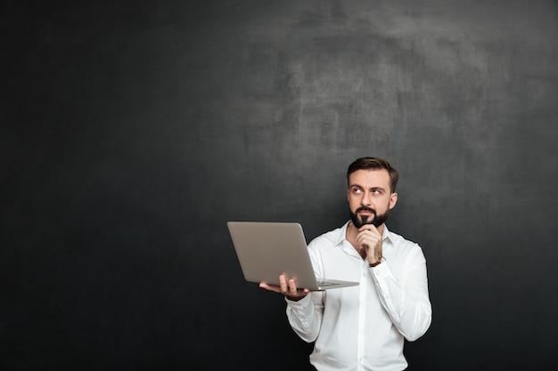 Geconcentreerde ongeschoren man die omhoog kijkt en zijn kin aanraakt, geïsoleerd over een donkergrijze muur