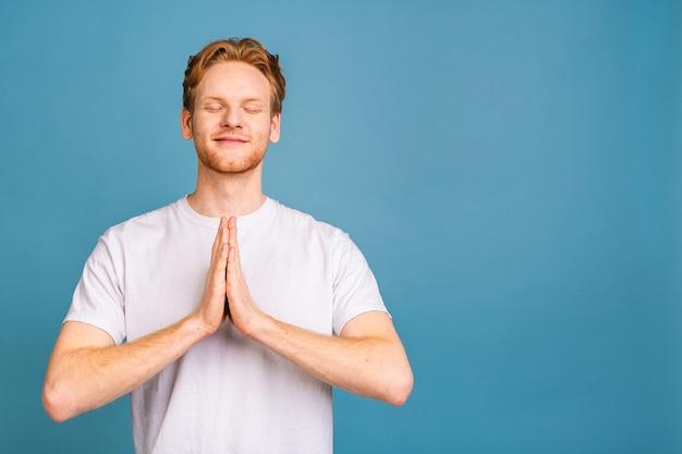 Geconcentreerde ontspannen man, ontspannen tijdens het mediteren, proberen balans en harmonie te vinden