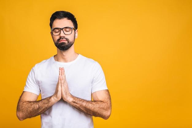 Geconcentreerde ontspannen persoon, staande met gesloten ogen, ontspannen tijdens het mediteren, proberen balans en harmonie te vinden.