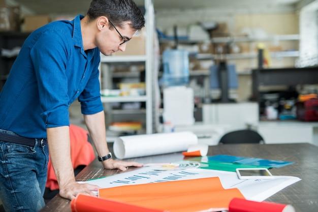 Geconcentreerde ontwerper die aan papier denkt om af te drukken