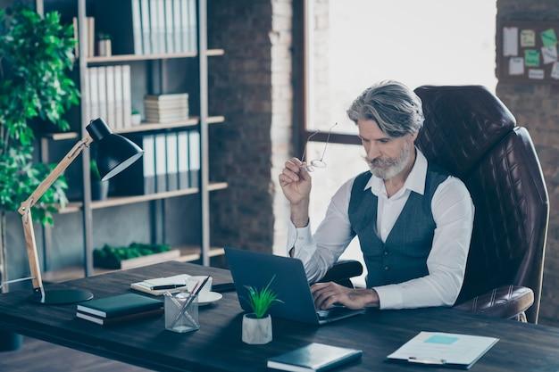 Geconcentreerde oude manager zit bureau laptop gebruikt in kantoor