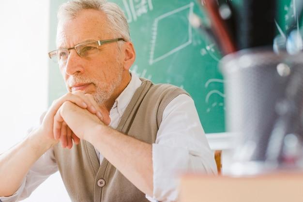 Geconcentreerde oude professor die weg in klaslokaal kijkt